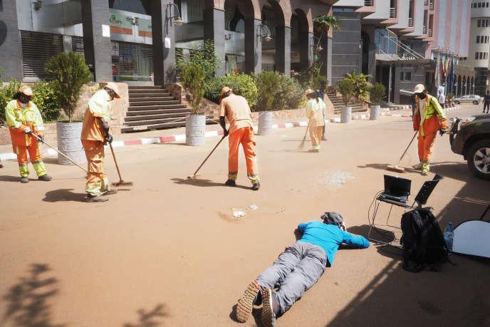 Les derniers bris de verre liés aux échanges de tirs de l'attaque terroriste sont balayés de l'allée qui mène jusqu'à l'entrée principale de l'hôtel, le 22 novembre.