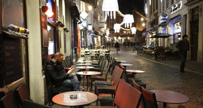 Un homme consulte son smartphone dans une rue du centre de Bruxelles, le 23novembre2015.