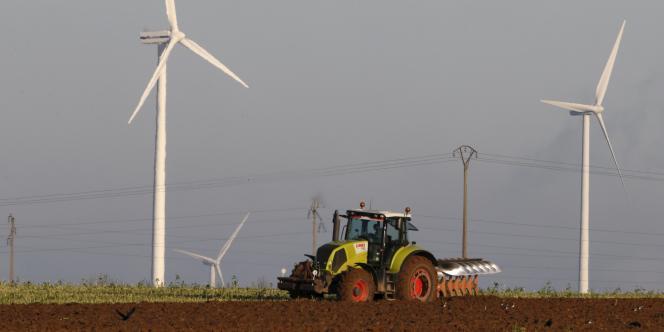 Un agriculteur devant des éoliennes à Vauvillers, près d'Amiens, en novembre 2013.