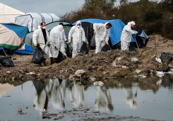 Des agents municipaux nettoient la « jungle » de Calais, le 12 novembre.