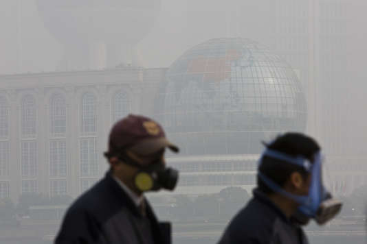 Dans le centre de Shanghaï, la population porte des masques tout en marchant face au quartier financier de Pudong.