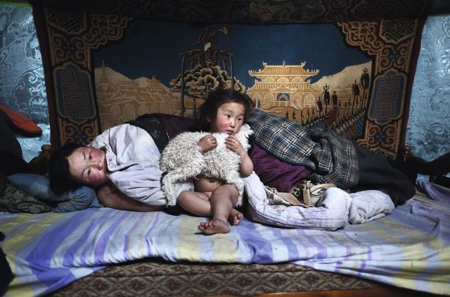Arkhangai, Mongolie, mars 2011. Erdene Tuya et son fils de 3 ans, Tuvchinj, au réveil. Dans les bras de l'enfant, un agneau qui dort avec eux.