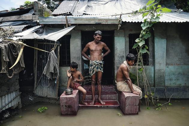Debnagar, Bangladesh, août 2011. Les villageois du district de Satkhira, contemplent la montée des eaux. La rivière Betna est sortie de son lit comme chaque année depuis neuf ans et les habitants se sont habitués à vivre dans ces conditions cinq mois par an. Très touché par les cyclones, le Bangladesh fait partie des pays les plus affectés par le réchauffement climatique.