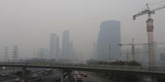 Des voitures se dirigent vers le quartier d'affaires de Pékin, en Chine, sous un épais brouillard ce jour-là, le 28 novembre, à deux jours de l'ouverture de la COP21 à Paris.