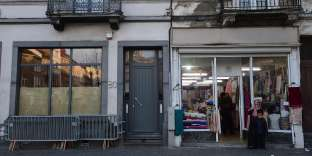 Two people are seen outside the Abdeslam family's apartment (C) in Brussels' Molenbeek district, close to the Town's Square where a vigil was earlier held, on  November 18, 2015. Two brothers from the Abdeslam family have been linked with the November 13 series of attacks on Paris -- Brahim one of the suicide bombers, and Salah who is still being hunted by police. Over 129 people were killed in the attacks on the French capital. AFP PHOTO/EMMANUEL DUNAND / AFP / EMMANUEL DUNAND