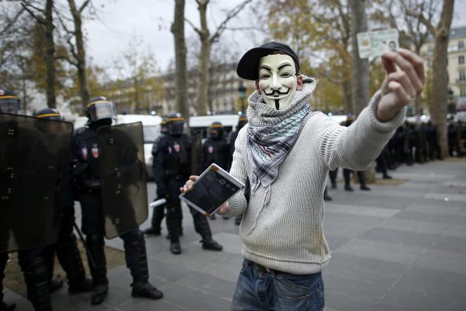 Un manifestant porte le masque de Guy Fawkes, symbole du groupe Anonymous, lors du rassemblement à Paris en marge de la COP21, dimanche 29 novembre.