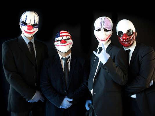 Quatre figurants déguisés à l'effigie des personnages de Pay Day 2 Crimewave Edition, un jeu de braquage sorti sur PlayStation 4 et Xbox One.