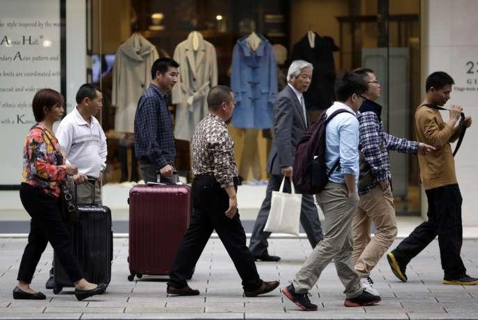 Des touristes font des achats dans une rue commerçante de Tokyo le 17 novembre 2015.