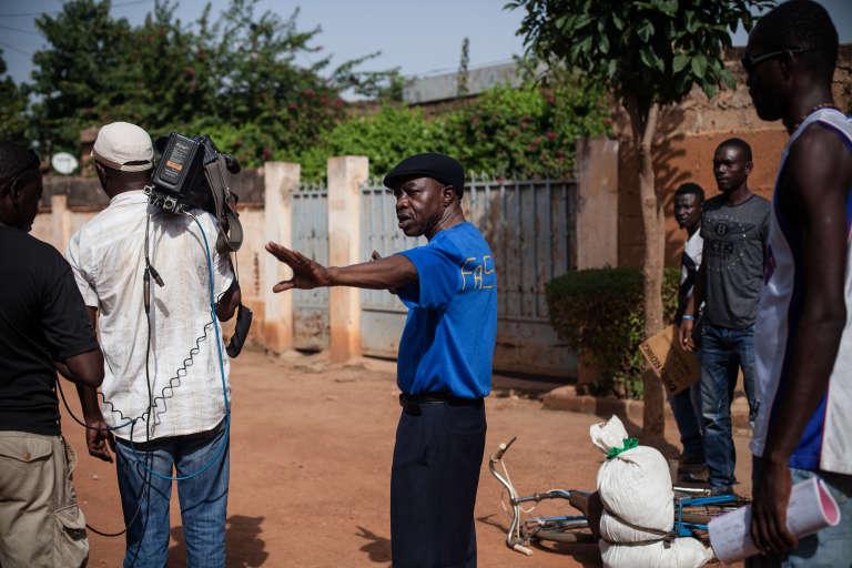 """Le réalisateur burkinabé Missa Hébié sur le tournage de sa série """"Stop corruption"""" dans une rue d'Ouagadougou."""