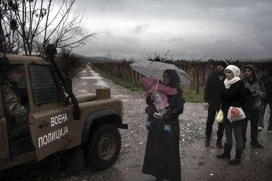 Une famille de réfugiés syriens, qui vient de franchir la frontière grecque à Idomeni, face à la police macédonienne, le 27 novembre.