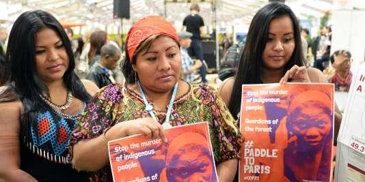 Des femmes de la communauté Embera, originaires du Panama, brandissent des pancartes qui demandent la fin des pratiques économiques qui mettent en danger les indigènes, à l'occasion de la COP21 à Paris.