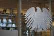 Two women stand next to a sculpture of the German federal eagle, as they watch a session of the Bundestag, the German lower house of parliament, in Berlin, Germany, December 2, 2015, during a debate on the country's role in the campaign against Islamic State.  German support for military involvement in the campaign against Islamic State has risen sharply with 42 percent backing action, a poll showed on Wednesday.  In direct response to a French appeal for solidarity after the attacks in Paris which killed 130 people, Germany has joined other countries in stepping up its role in the military campaign against IS insurgents in Syria.     REUTERS/Fabrizio Bensch