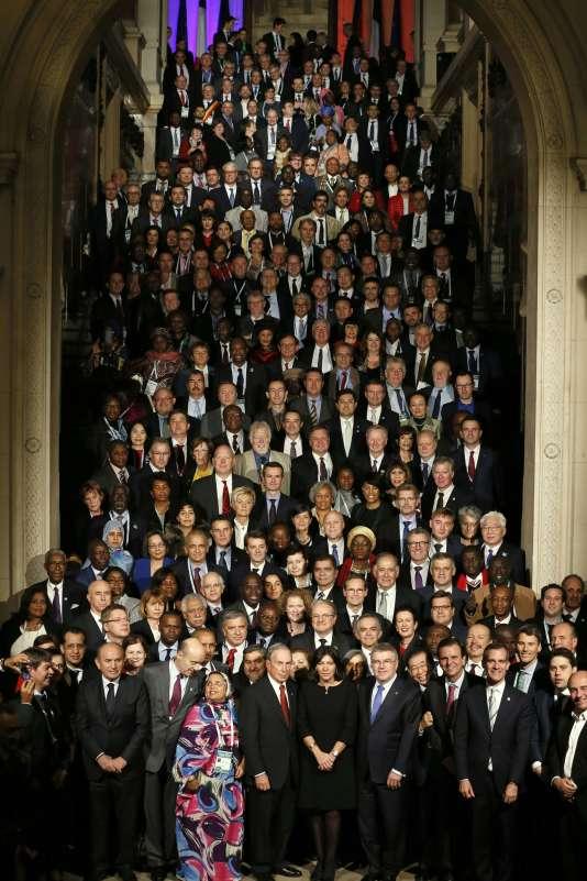 Anne Hidalgo, la maire de Paris, et Michael Bloomberg, ancien maire de New York, entourés de plusieurs centaines d'élus locaux venus du monde entier, posent dans le grand escalier de l'Hôtel de ville de Paris, le 3décembre.