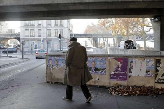 Un homme passe devant des affiches électorales à Lyon le 3 décembre 2015.