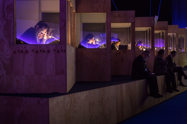 """Les interprètes et traducteurs dans leur cabine de la salle plénière """"La Loire"""". L'interprétation et la traduction lors des séquences formelles de la COP21 sont assurées par le secrétariat de la Convention-cadre des Nations unies sur les changements climatiques (CCNUCC)."""