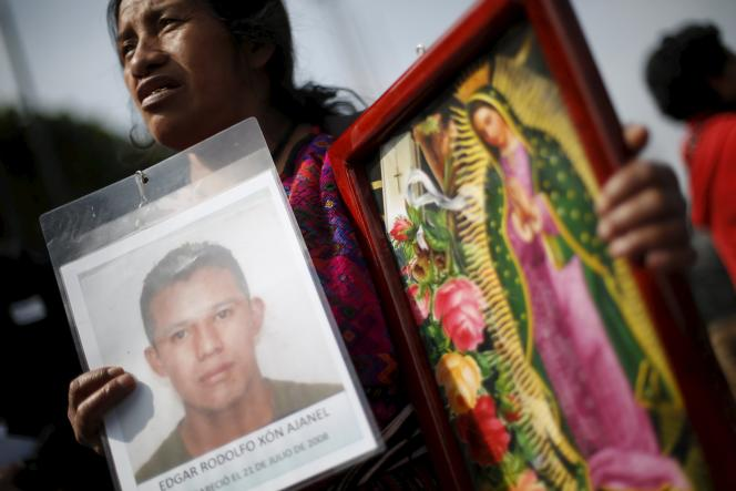 Une mère brandit le portrait de son fils, disparu alors qu'il marchait vers Mexico, en décembre 2015.