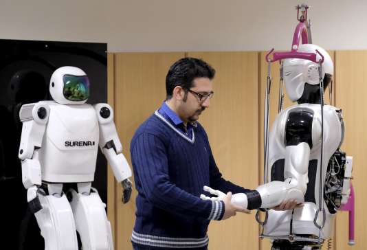 An engineer works on Surena 3 humanoid robot (R) next to Surena 2 robot, in a lab at Tehran University, Iran December 6, 2015. The University of Tehran has developed a humanoid robot that weighs 98 kg. It can navigate uneven terrain and detect faces. REUTERS/Raheb Homavandi/TIMA  ATTENTION EDITORS - THIS IMAGE WAS PROVIDED BY A THIRD PARTY. FOR EDITORIAL USE ONLY.