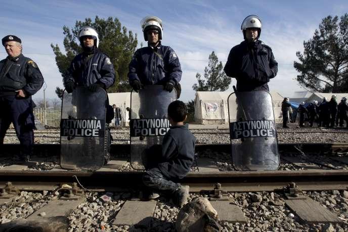 Un enfant migrant face à la police grecque à la frontière entre la Grèce et la Macédoine à Idomeni, le 7 décembre 2015.