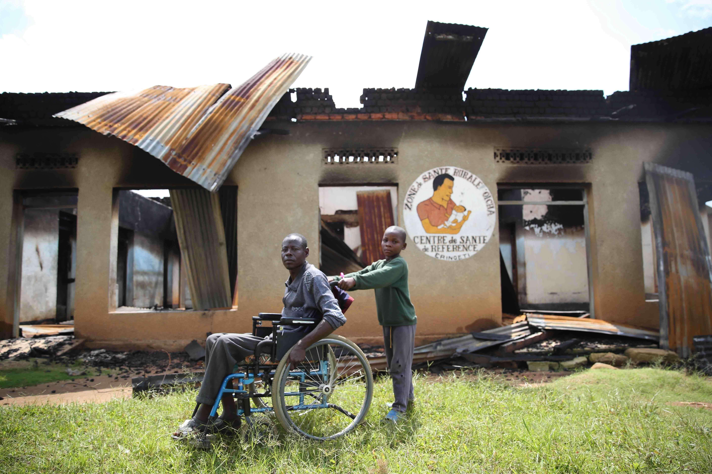 Un enfant pousse un invalide en fauteuil roulant devant les décombres de l'hôpital d'Eringeti, attaqué par les rebelles ougandais ADF-Nalu le 30 novembre 2015.