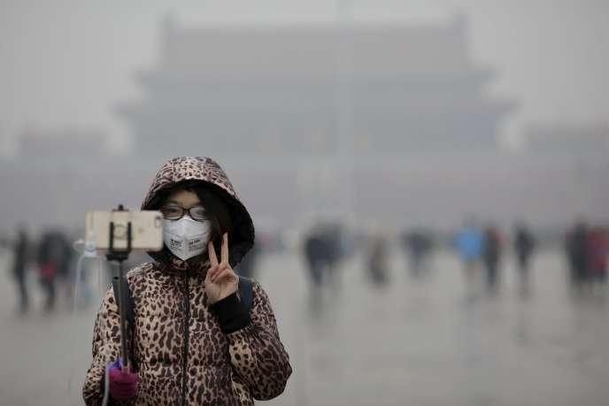 Une femme sur la place Tiananmen, à Pékin, pendant l'alerte rouge à la pollution, le 9 décembre.