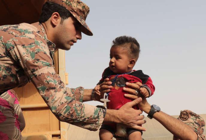 Des soldats jordaniens portent un jeune réfugié syrien, à Roqban, le 10 septembre 2015.
