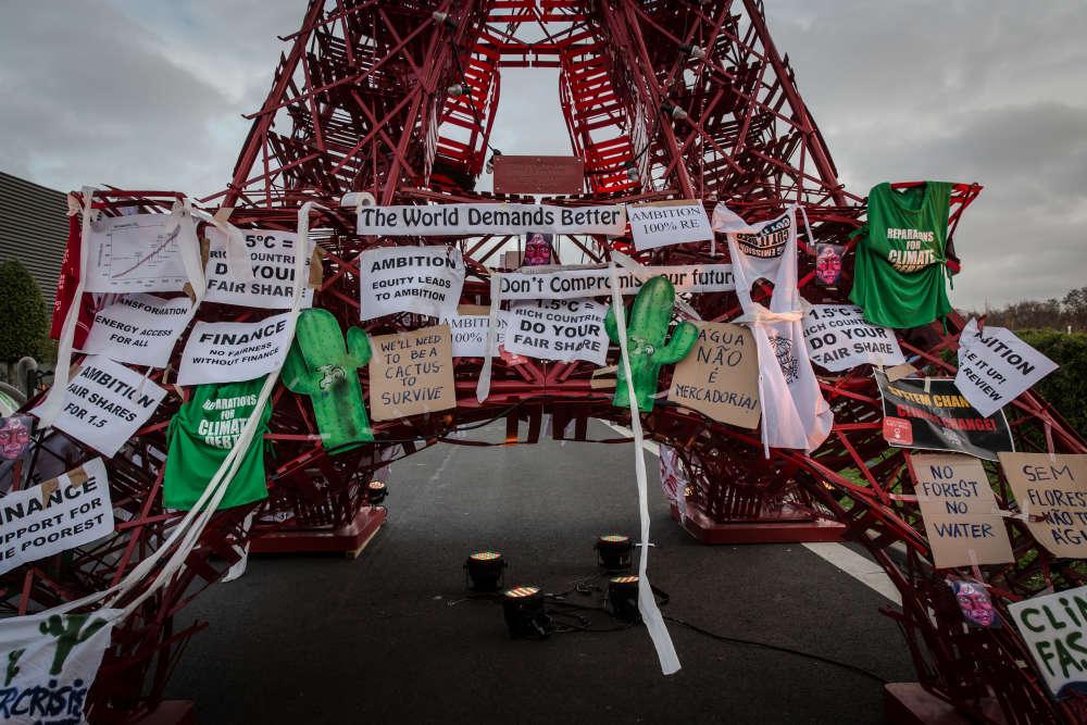 Une réplique de la tour Eiffel de la COP21, recouverte de slogans après les différentes interventions des ONG.