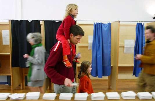 Un père de famille accompagné de ses enfants, prend des bulletins de vote, le 21 avril 2002 à Lyon, à l'occasion du premier tour de l'élection présidentielle.