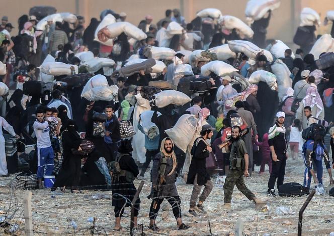 Les habitants de Akcakale, en Syrie, se pressent à la frontière turque pour fuir les affrontements entre combattants kurdes et membres de l'Etat islamique. Les djihadistes se mêlent à la foule pour forcer la population à regagner la ville.