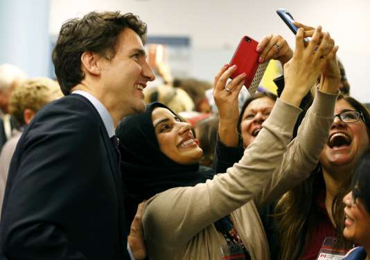 Canada's Prime Minister Justin Trudeau (L) poses with airport staff as they await Syrian refugees to arrive at the Toronto Pearson International Airport in Mississauga, Ontario, December 10, 2015. After months of promises and weeks of preparation, the first planeload of Syrian refugees was headed to Canada on Thursday, aboard a military plane to be met at Toronto's airport by Trudeau. REUTERS/Mark Blinch