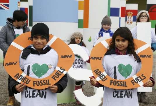 """Des enfants portent des bouées sur lesquelles est écrit : """"Adieu, énergies fossiles"""" lors d'une démonstration organisée par l'ONG Avaaz."""