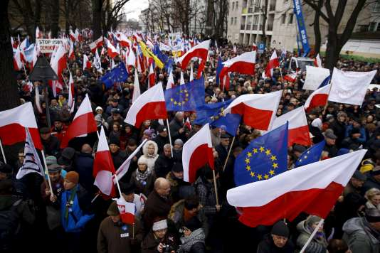 People hold European Union (EU) and Polish national flags during an anti-government demonstration in front of the Constitutional Court in Warsaw, Poland December 12, 2015. REUTERS/Kacper Pempel