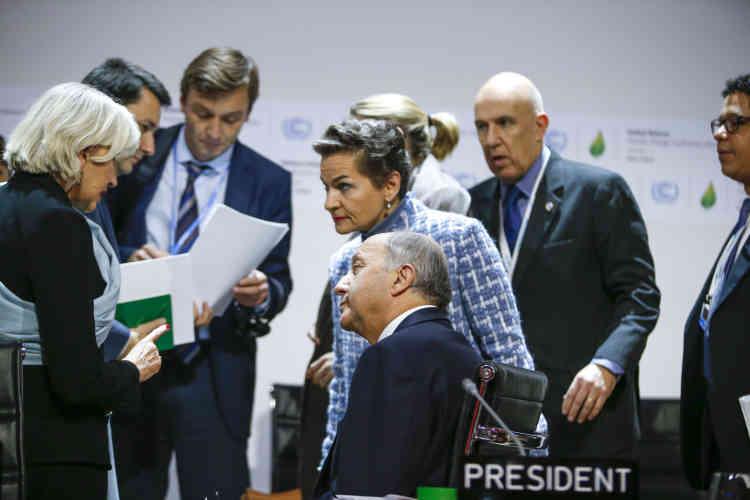 Laurence Tubiana, Laurent Fabius et Christiana Figueres, secrétaire exécutive de la Convention-cadre des Nations unies sur les changements climatiques, retournent à à la salle plenière.