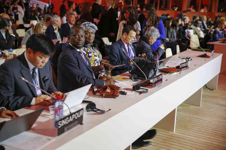 Des délégués de Singapour, de Sierra Leone et des Seychelles attendent l'annonce de l'adoption, ou pas,  du projet d'accord final de la COP21.