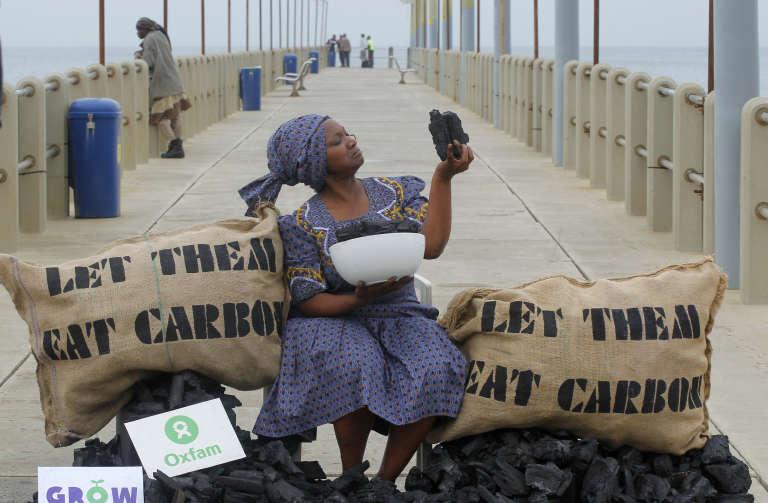 Busi Ndlovu, membre de l'ONG Oxfam, proteste contre l'utilisation du charbon de bois, sur une plage de Durban, en Afrique du Sud.