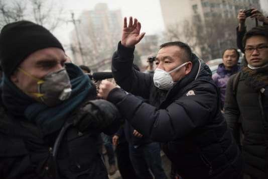 La police chinoise repousse manifestants et journalistes devant le procès de l'avocat Pu Zhiqiang à Pékin le 14 décembre.