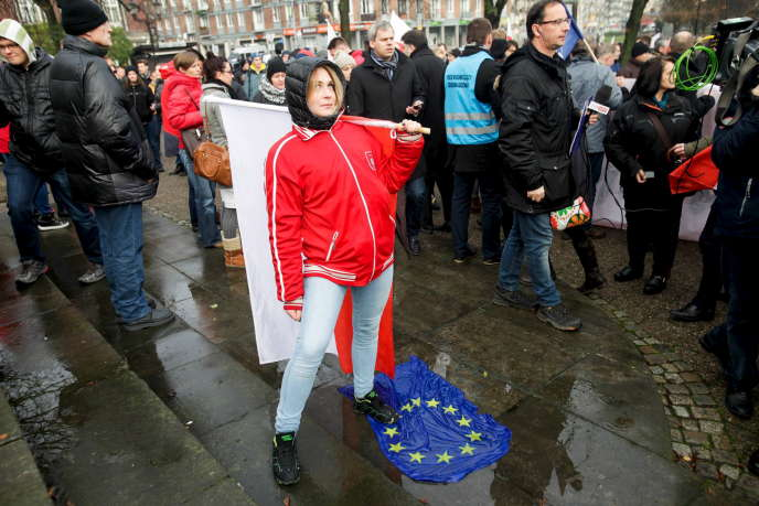 Une femme marche sur un drapeau européen lors d'une marche anti-migrants à Gdansk en Pologne le 22 novembre 2015.