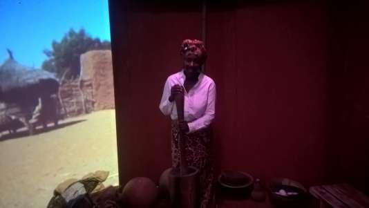 Sani, dans le décor du Sahel, accueille le spectateur en pilant du mil.