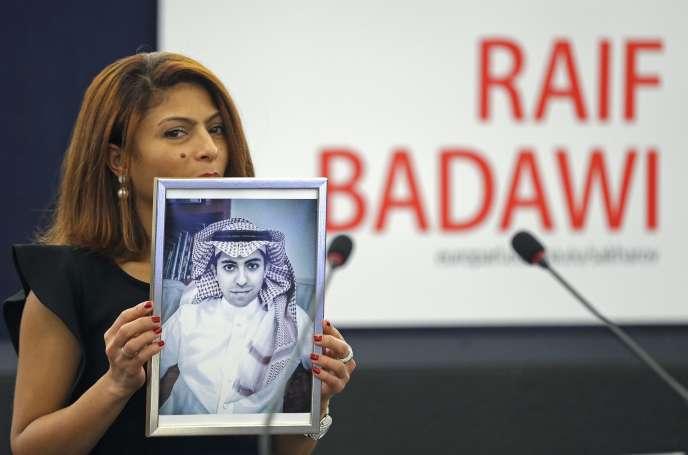 Ensaf Haidar pose avec la photo de son époux – leblogueur saoudien Raïf Badawicondamné en 2014 à dix ans de prison et mille coups de fouet pour « injures envers l'islam »– au parlement de Strasbourg en décembre 2015, lors de la cérémonie pour la remise du prix Sakharov.