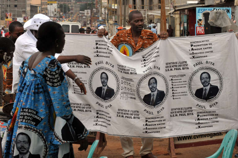 Supporters of outgoing president Paul Biya dressed with clothes with the effigy of their leader, hold a banner with his portraits on October 5, 2011 on a Yaounde street. Presidential elections in Cameroon will take place on October 9 with 23 candidates running for the top position including Biya. AFP PHOTO / SEYLLOU DIALLO / AFP / SEYLLOU DIALLO