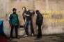 Deux migrants dans la jungle de Calais entourent, le 12 décembre, le graffiti de Banksy représentant Steve Jobs, fils d'un immigré syrien.