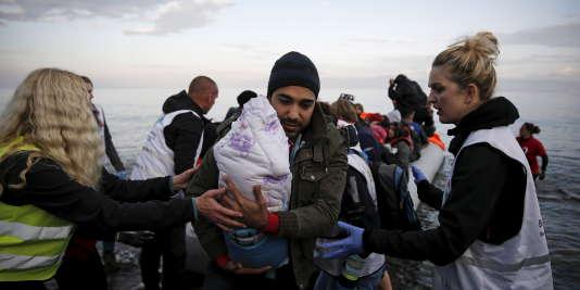 Un réfugié syrien arrive avec son enfant sur l'île de Lesbos, en Grèce, le 10 novembre.
