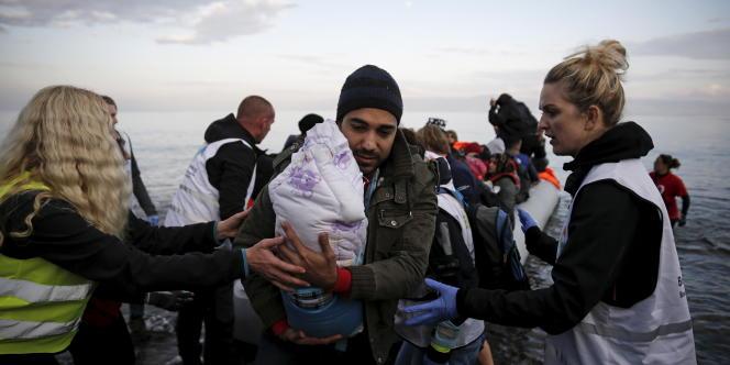 Un Syrien arrive à Lesbos, le 10 novembre 2015 avec son enfant nouveau né dans les bras.