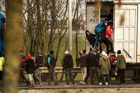 Des migrants entrent dans la remorque d'un camion sur le site d'Eurotunnel, à Calais, le 17 décembre.