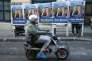 A man driving a moped passes electoral posters of Far right National Front party regional leader for southeastern France, Marion Marechal-Le Pen,  in Marseille,  southern France, Thursday, Dec.10, 2015. The head of France's far-right National Front vowed on Thursday to bring suit against the French state over the situation in Calais, where thousands of migrants are camped in hopes of reaching Britain. Marine Le Pen, in the race for president of the northern region, went on the offensive three days before Sunday's elections, and a day after a poll suggested she might lose. (AP Photo/Claude Paris)
