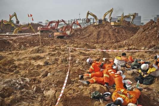 Les équipes de secours sur les lieux du glissement de terrain qui a causé la destruction de dizaines de bâtiments et pris au piège plus de 70 personnes, dimanche, en périphérie de Shenzen dans le sud de la Chine.