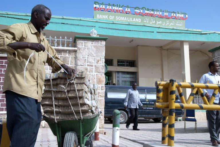 Un homme sort de la Banque du Somaliland avec une brouette chargée de billets de Shillings, à Hargeisa en décembre 2015.