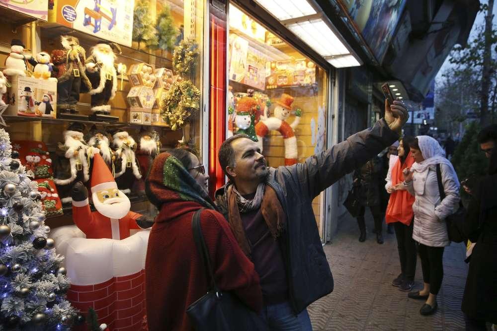 Un couple d'Iraniens se prend en photo devant une vitrine de Noël. Environ 120 000 chrétiens vivent en Iran et comptent trois de leurs représentants au Parlement.