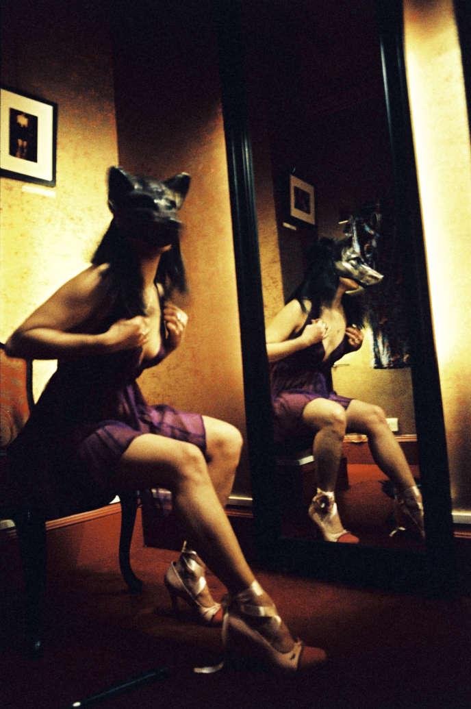 Une femme essaye un masque de loup, dans un sexshop de Londres, en 2002.