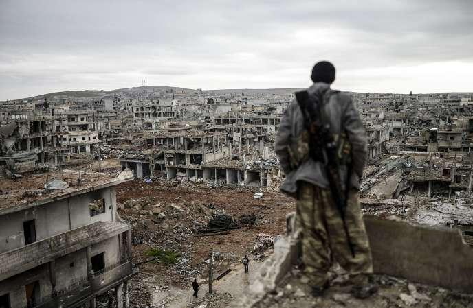 Musa , 25 ans, tireur d'élite kurde, au sommet d'un bâtiment qui surplombe la ville syrienne détruite de Kobané, le 30 janvier 2015.