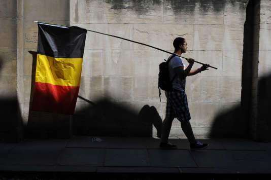 Un homme porte un drapeau belge le jour de la fête nationale à Bruxelles le 21 juillet 2013.
